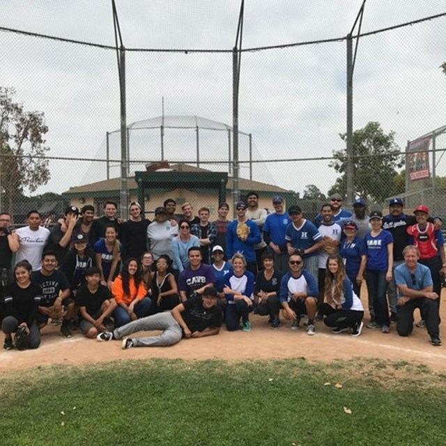Staff have fun in a baseball game on campus!